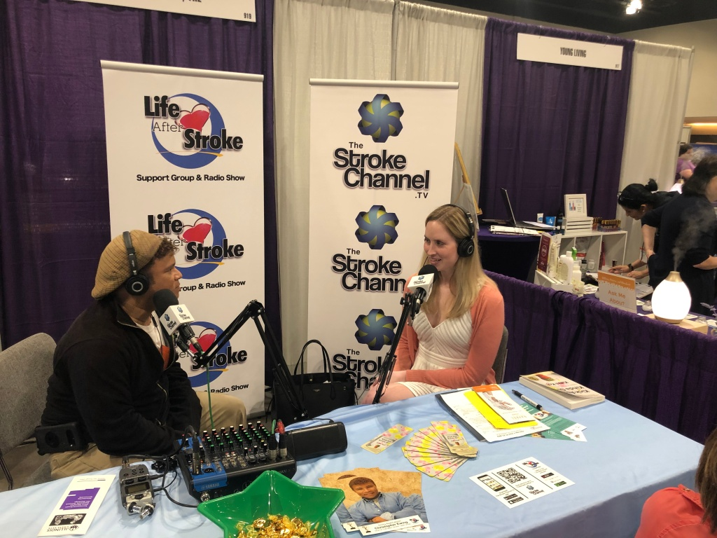 [Image description (alt text provided in image): Ashley is sitting at a table with the Life After Stroke and The Stroke Channel TV banners behind her, and to the left is Christopher Ewing.  They both have microphones and are wearing headphones as Christopher Ewing interviews Ashley.  This interview is available wherever you find your podcasts, on the show Life After Stroke.]